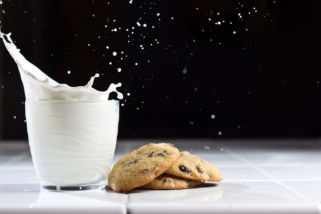 A milk glass with cookies on display
