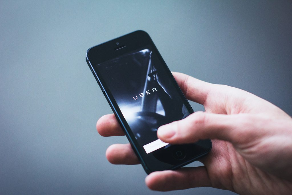 A consumer using Uber application on smartphone