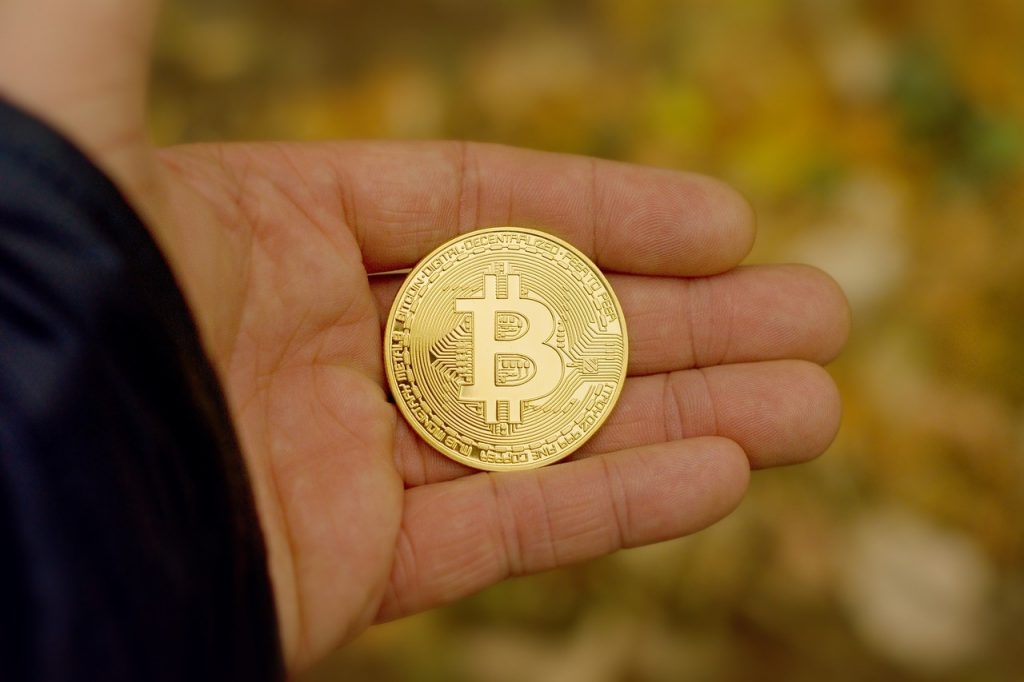Man holding fictional bitcoin currency in his hand