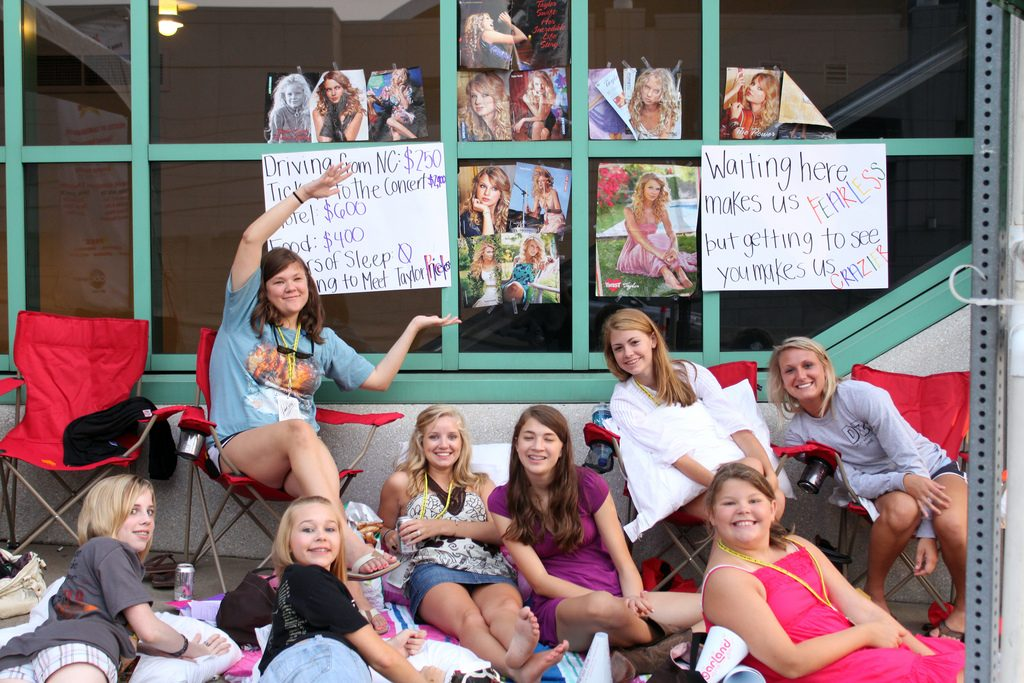 Young Taylor Swift fans waiting outside with her posters